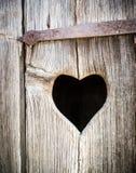 Wooden heart. At an antique restroom-door Stock Photo