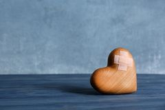 Wooden heart with adhesive plasters on table. Space for text royalty free stock image