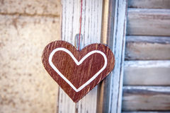 Wooden heart  on a background of blue shutters. Wooden heart hanging on a background of blue shutters in soft focus Royalty Free Stock Photo