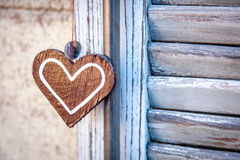 Wooden heart  on a background of blue shutters. Wooden heart hanging on a background of blue shutters in soft focus Royalty Free Stock Photography
