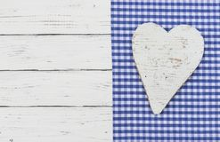 Oktoberfest background with rustic blue checked fabric and white heart. Wooden heart on blue textile border and white wood with copy space for Octoberfest or stock photos