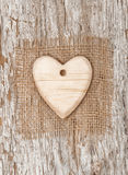 Wooden heart with burlap textile on the old wood Royalty Free Stock Images