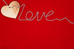 Wooden heart and chain on red background for St. Valentine`s day Royalty Free Stock Image