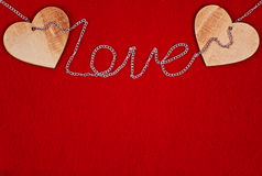 Wooden heart and chain on red background for St. Valentine`s day Stock Images