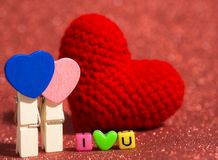 Wooden heart clip with red yarn heart and I Love You from bead colorful on the red floor and background. copy space for text. Valentine's day, love concept Stock Image