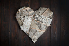 Wooden heart on dark wood background Royalty Free Stock Images