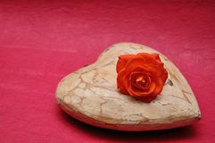A wooden heart displayed with an orange rose. On a pink background stock photos