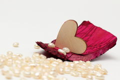 Wooden heart on driftwood mahogany with pearls on the background Royalty Free Stock Images