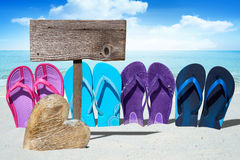 Wooden heart and flip flops on beach Stock Images
