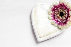 Wooden heart and a flower on a white painted background, love sy. Mbol for valentines or mothers day, copy space, selected focus Royalty Free Stock Image