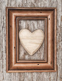 Wooden heart in frame on the old wood Stock Image