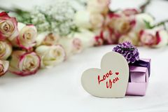 Wooden Heart Gift Box and Beautiful Roses. Gift box and Love You wooden heart card in front of a beautiful bouquet of  red and white roses in the background Royalty Free Stock Photos