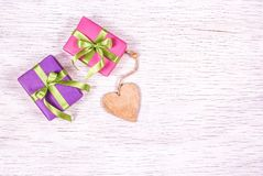 Wooden heart and gift boxes on a white background. Copy space. Bright gift boxes with ribbons. Stock Image