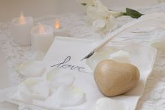 Wooden heart, goose feather, candles and flower stock images