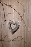Wooden heart hanging on dry twigs on wood Stock Images