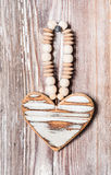 Wooden heart hanging on a rustic plank Royalty Free Stock Images