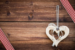 Wooden heart hanging on sun burned planks. With red white ribbon Stock Images