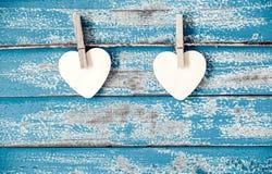 Wooden heart hanging on vintage blue wood background Stock Images