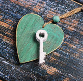 Wooden heart and a key on shabby old background Stock Image