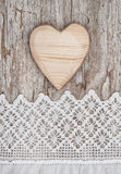 Wooden heart on the lace fabric and old wood Stock Image