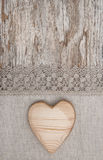 Wooden heart on the lace fabric and old wood Stock Photos