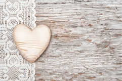 Wooden heart on lacy cloth and old wood Royalty Free Stock Photo