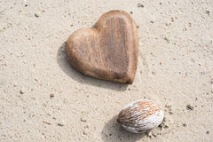 Wooden heart and nut on the sand on the beach Stock Photos