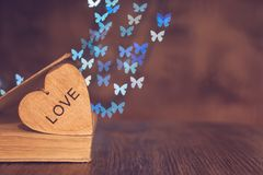 Wooden heart with an old book on the table and a background of bokeh made of butterflies. Valentine`s Day. stock image