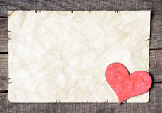 Wooden heart on old paper Stock Photography