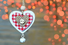 Wooden heart ornament against Christmas lights and wooden background Stock Photos
