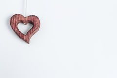Wooden heart ornament symbolizing love. And romance in the upper left corner of a blank white background with copyspace for your message to a sweetheart or Royalty Free Stock Images