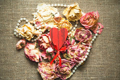 Wooden heart over dry roses Royalty Free Stock Photography