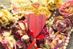 Wooden heart over dry roses Stock Photos