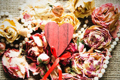 Wooden heart over dry roses Stock Photo