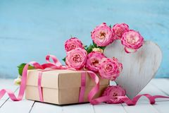 Wooden heart, pink rose flowers and gift box on turquoise table. Beautiful greeting card for Birthday, Woman or Mothers Day. Stock Image