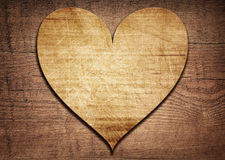 Wooden heart placed on a brown wood board.  Royalty Free Stock Images