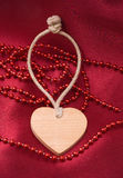 Wooden heart and red beads Royalty Free Stock Image