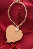 Wooden heart and red beads Stock Image