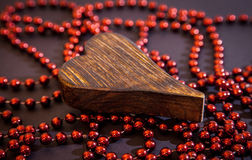 Wooden heart on red beads Royalty Free Stock Images