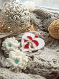 Hygge holiday composition. Wooden heart with textile details, handmade soap, decorative balls, knitted scarf on windowsill stock photo