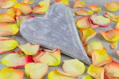 Wooden heart and rose petals Royalty Free Stock Image