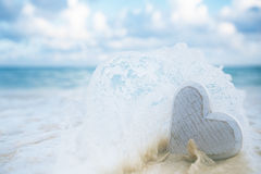 Wooden heart in sea waves, live action. Shallow dof Royalty Free Stock Photography