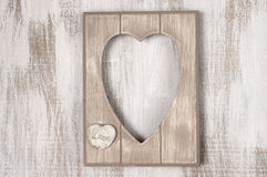 Wooden heart shape frame. Empty vintage wooden heart shape photo frame on rustic wood background. Top view point Royalty Free Stock Image