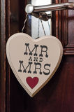 Mr and Mrs wooden heart. A wooden heart shape hangs from a door and contains the words Mr and Mrs Royalty Free Stock Photo