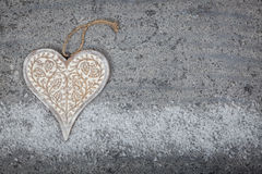 Wooden heart on stone background. Carved wooden on heart on stone background with snow Stock Image
