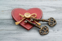 Wooden heart and two ancient keys on a natural wooden background Royalty Free Stock Photos