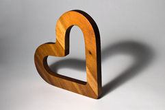 Wooden heart. Upright wooden heart casting heart-shaped shadow giving appearance of two hearts Royalty Free Stock Photo