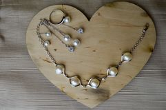 A wooden heart for Valentine`s Day with silver ornaments, earrings, rings, necklaces with pearls, diamonds, precious stones, rhin Stock Images