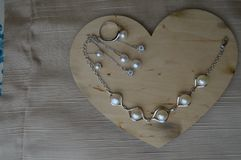 A wooden heart for Valentine`s Day with silver ornaments with pearls and diamonds. On a background of beige fabric royalty free stock images