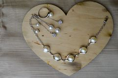 A wooden heart for Valentine`s Day with silver ornaments with pearls and diamonds. On a background of beige fabric royalty free stock photo